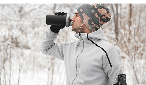 Man Drinking Water during Exercise in Winter