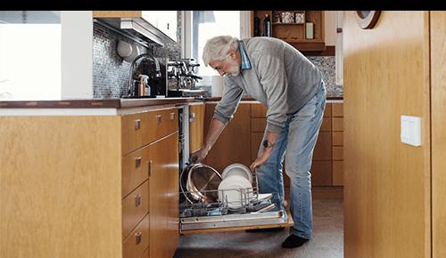 Older Man Loading Dishwasher
