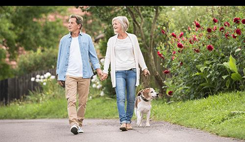 Older Couple Walking Dog