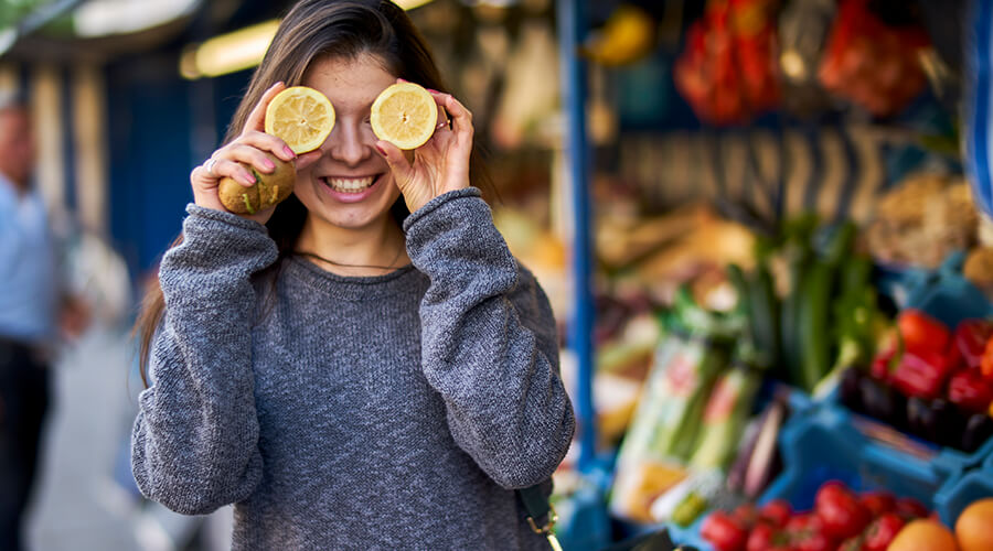 Woman smiling at food market holding sliced lemons in front of her eyes