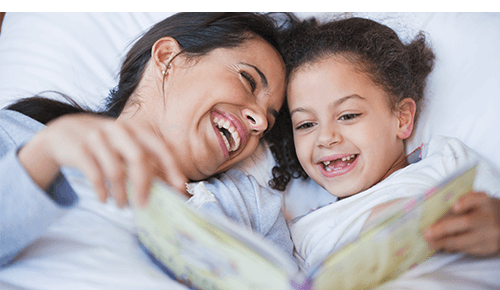 Mother and Daughter Reading Book Bedtime