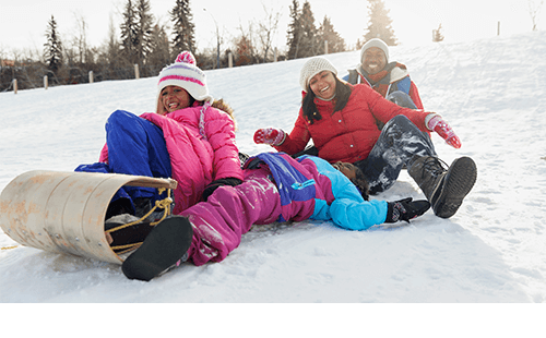 Family sledding on snowy hill