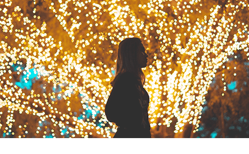 Woman walking by holiday lights