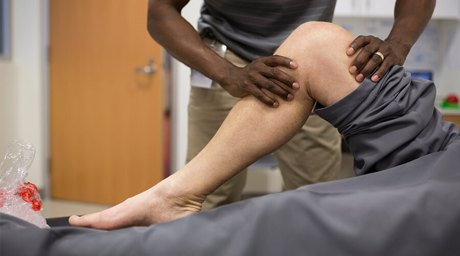 Physical therapist examining a patient's hurt knee