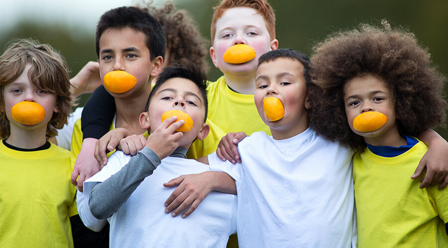 Group of children hugging and smiling with orange slices in their mouths