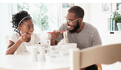 Father and Daughter Eating Dinner Together