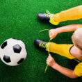 Person tying shoe next to soccer ball on field