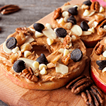 Apple slice with peanut butter, nuts and chocolate chips on top