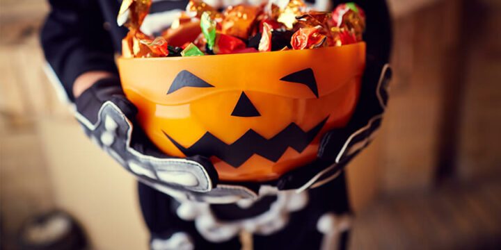 Child in costume holding jack-o'-lantern bucket full of Halloween candy