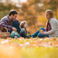 Parents and child sitting on blanket outdoors during fall season