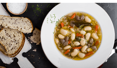 bowl of Cabbage and White Bean Soup with Sausage with bread on the side