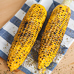 Two ears of grilled corn on kitchen cloth