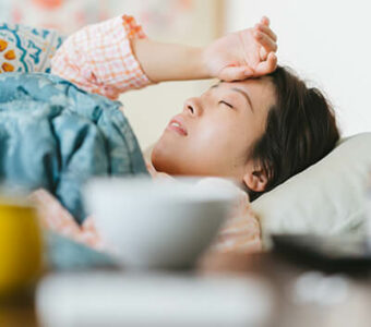 Sick person lying in bed with hand to forehead