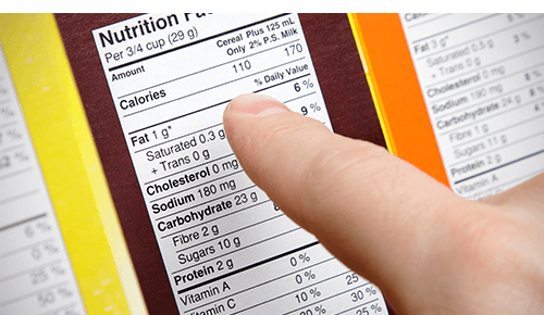 person looking at nutrition facts on box of food