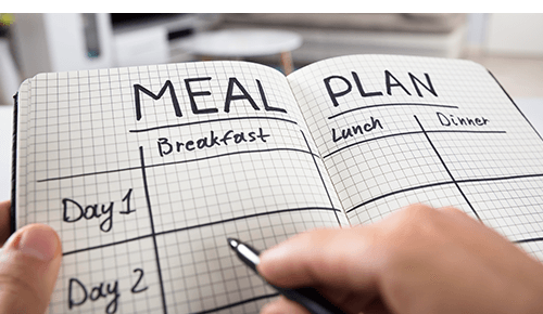 Person writing in meal plan food diary