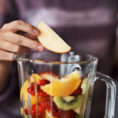 Closeup of person making a fruit smoothie in a blender