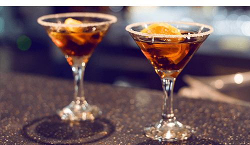 Martini glasses with a cocktail and fruit slice