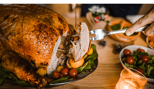 Person slicing and serving Thanksgiving turkey