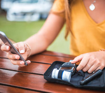 Diabetic person measuring blood sugar levels and looking at phone