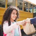 Adult handing a brown paper lunch bag to child in front of school bus