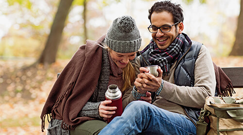 Couple laughing and drinking from thermos outdoors in the fall