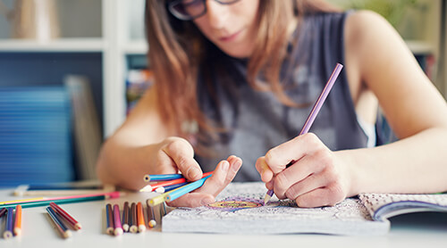 Person coloring in coloring book using colored pencils