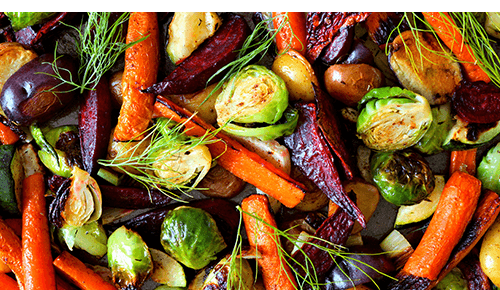 Pan full of roasted vegetables with rosemary on top