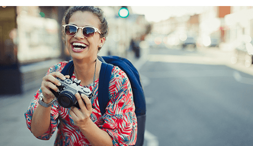 Woman laughing while holding camera in city