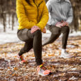 Two people stretching their legs outside before exercising