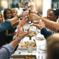 Group of people toasting with glasses at gathering
