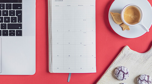 Closeup of calendar planner next to laptop and coffee with cookies
