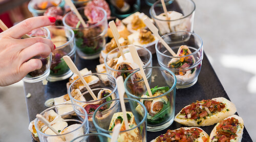 Person choosing from a variety of appetizers on table