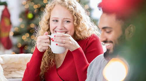 Woman sipping coffee while laughing with a man