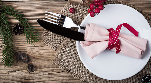 Knife and fork wrapped in a pink napkin with red ribbon on place setting
