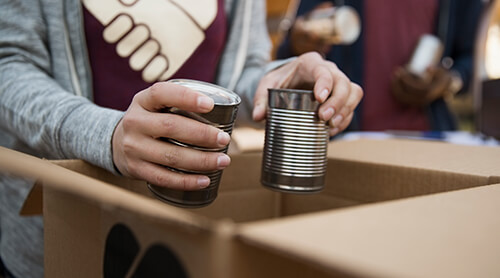 Closeup of person putting metal food cans in cardboard box