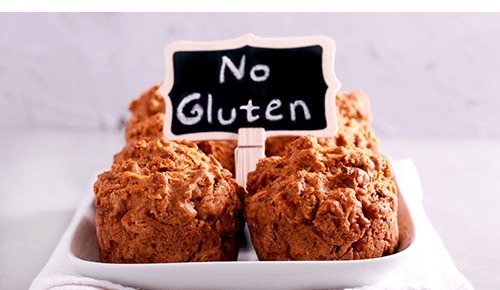 Plate full of muffins with sign that says No Gluten