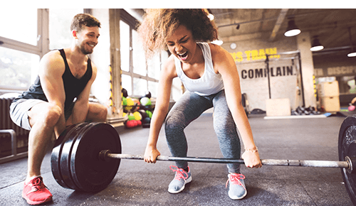 Person lifting a weight with help from another person