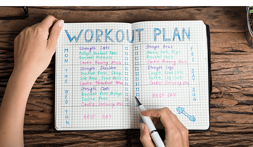 Person writing in workout plan journal