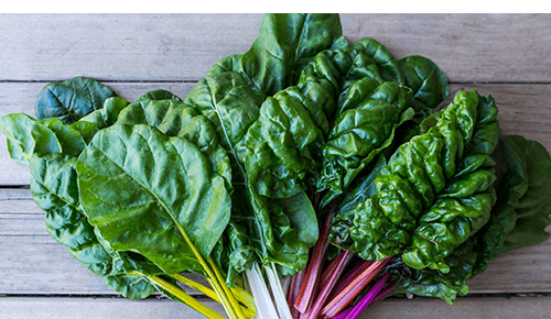 Variety of leafy greens on wooden table
