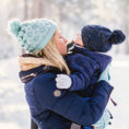 Mother holding baby, both wearing cold weather gear, in winter outside