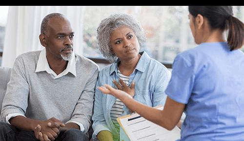 Couple talking to nurse holding clipboard