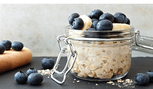 Mason jar wit oatmeal topped with blueberries