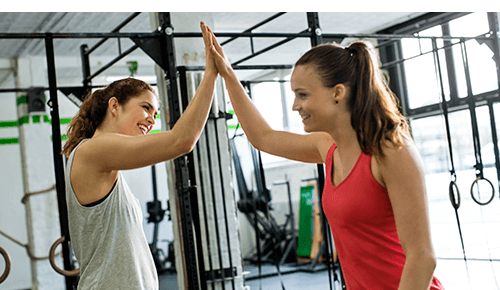 People high-fiving during exercise at a gym