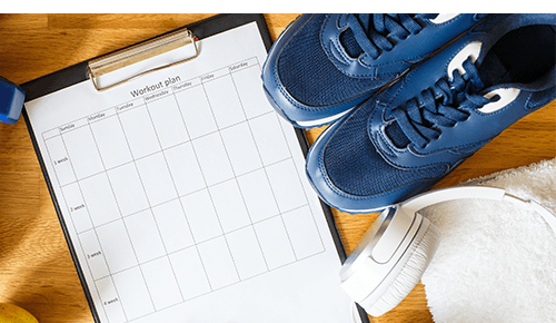 Exercise shoes, headphones and a clipboard with a blank workout plan on it