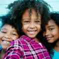 Three young children smiling into camera