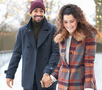 Couple holding hands while ice skating outdoors in the winter