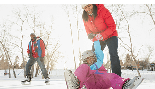 Woman helping her child as they fall while iceskating with man skating behind them
