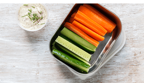 Container of cut raw veggies and a side of dipping sauce