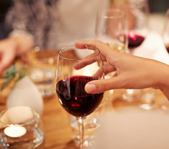 Closeup of a group of people holding wine glasses full of red wine around a dinner table