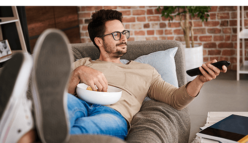 Man laying on couch holding remote control and a bowl of snacks